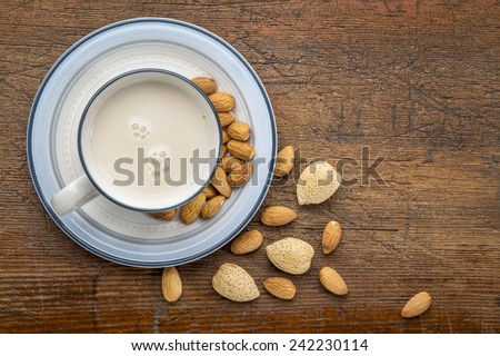 a cup of almond milk with almond nuts on a rustic barn wood table - stock photo