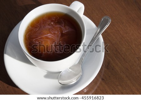 A cup of black coffee and milk on wooden table.