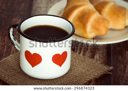 A cup of black coffee in an old enamel mug, breakfast croissants on background, vintage rustic table