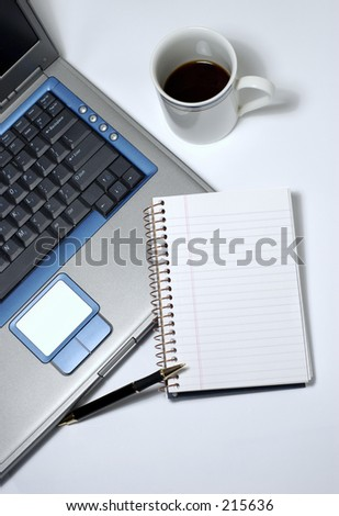A cup of black coffee, laptop, notepad and pen.