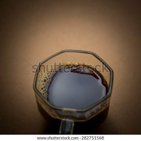 a cup of black coffee on wooden background