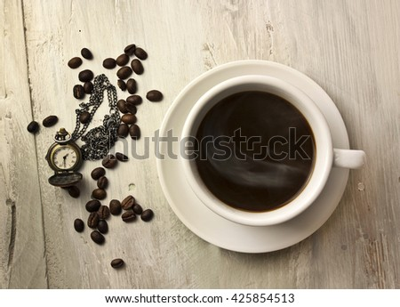 A cup of black coffee with a whiff of steam, with coffee beans and a vintage chain watch, shot from above on a wooden board texture, slightly toned in sepia; coffee time concept