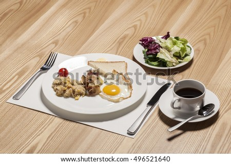 A cup of black coffee with bread, egg, salad, dish, fork, knife on the wood table in the hotel, seoul, korea.