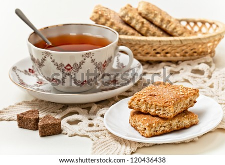 A cup of black tea and cookies on a plate with slices of sugar - stock photo