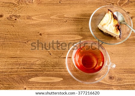 A cup of black tea in a transparent glass cup, and apple cake with spoon on rustic wooden table top. Top view. Flat. Copy space. - stock photo