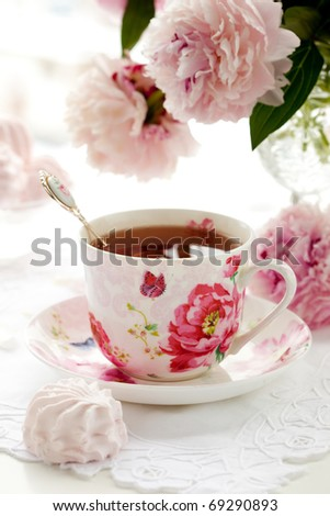 A cup of black tea,sweets and peonies - stock photo