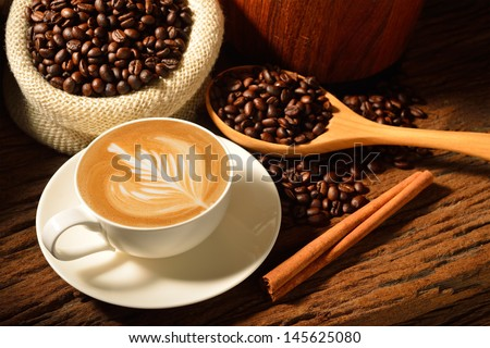 A cup of cafe latte and coffee beans - stock photo