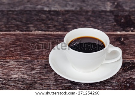 A cup of cafe latte on wooden table - stock photo