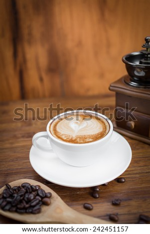 A cup of cafe latte with coffee beans and coffee mill, still life with coffee