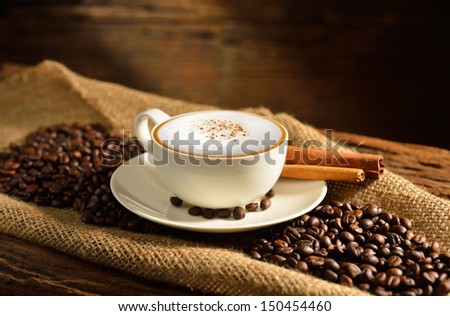 A cup of cappuccino and coffee beans on old wooden background - stock photo