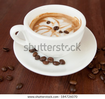 A cup of cappuccino and coffee beans on old wooden background