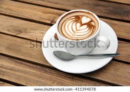 A cup of cappuccino coffee on top of wooden table, close up image - stock photo
