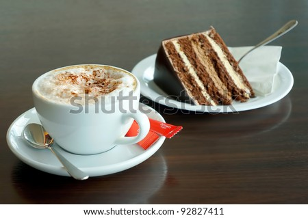 A cup of cappuccino coffee with slice of chocolate cake - stock photo