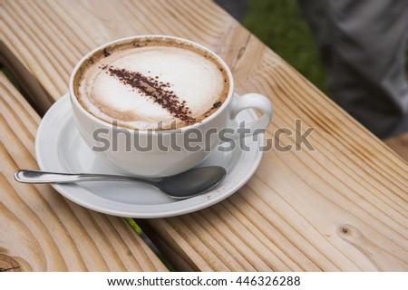 A cup of Cappuccino on top of a wooden bench table