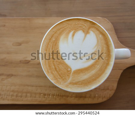 a cup of cappuccino over wooden table - stock photo