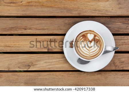 A cup of cappuccino top view, on wooden table - stock photo