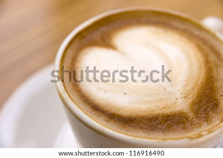 A cup of cappuccino with foam in shape of heart. Shallow DOF - stock photo