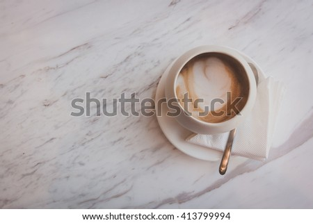 A cup of cappucino on a white table - stock photo