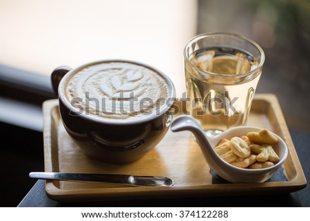 a cup of capuchino coffee and biscuits on table - stock photo
