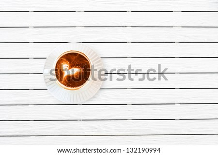 A cup of Capuchino coffee in a white cup on white wooden background with copy space. - stock photo