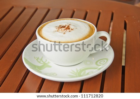A cup of Capuchino coffee in a white cup on wooden background.