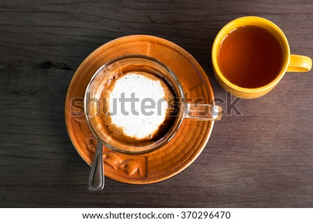 A cup of caramel cappuccino coffee in a transparent cup on wooden background with hot tea in yellow cup - stock photo