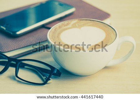 A cup of coffe with heart pattern in a white cup on, smartphone, leather notebook and eyeglasses on wooden  table.Close up.Vintage tone - stock photo