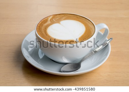 A cup of coffe with heart pattern in a white cup on wooden  table.Close up