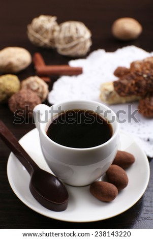 A Cup of coffee and a saucer with chocolates on doily, on the dark wooden smooth background