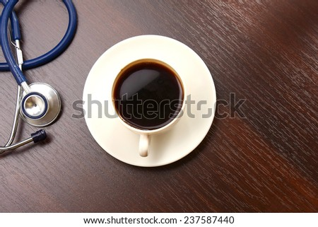 A cup of coffee and a statoscope on a desk, from above