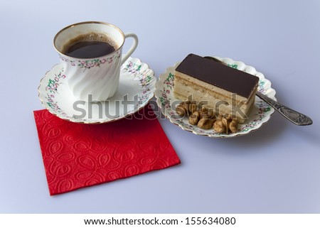A cup of coffee and coffee cake on a plate
