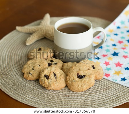 a cup of coffee and homemade cranberry oatmeal cookies on the table.