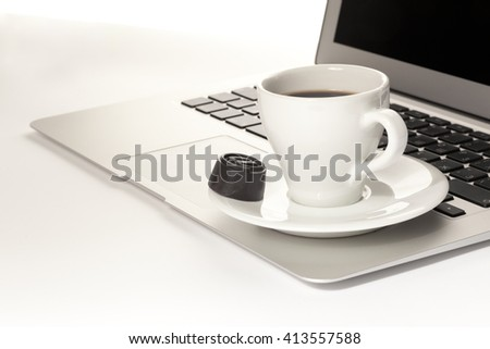 A cup of coffee and laptop on table - stock photo