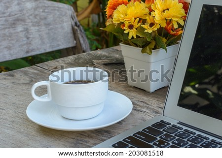 a cup of coffee and laptop on wooden table with flower - stock photo