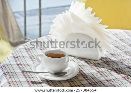 A cup of coffee and napkin on a table at an outdoor cafe - stock photo