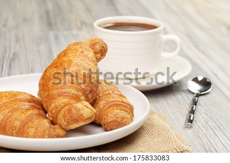 A cup of coffee and plate with croissants