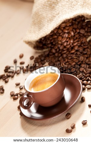 A cup of coffee and roasted coffee beans - stock photo