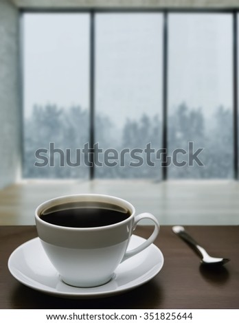 A cup of coffee and snowstorm view from large window on the background - stock photo