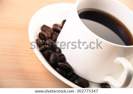 A cup of coffee and some coffee beans are on the table.