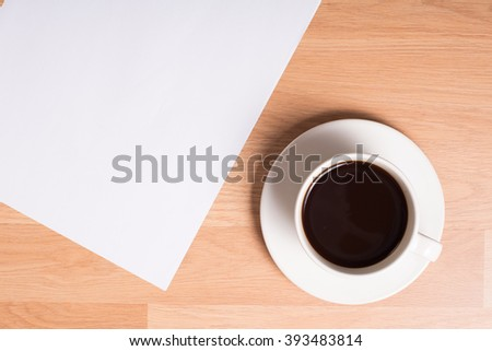 a cup of coffee and white paper