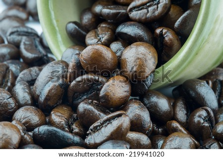 A cup of coffee arranged with raw coffee bean in close-up view - stock photo