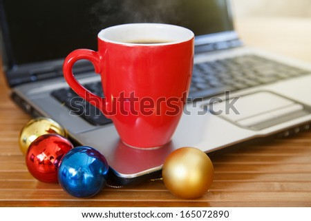 A cup of coffee at laptop - stock photo