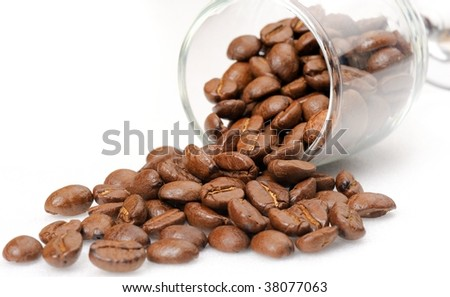 a cup of coffee beans scattered on a white background