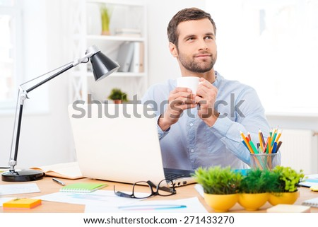 A cup of coffee for new ideas. Handsome young man in shirt holding a cup of coffee and looking away while sitting at his working place - stock photo