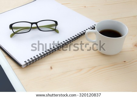 a cup of coffee ,glasses ,notebook and tablet