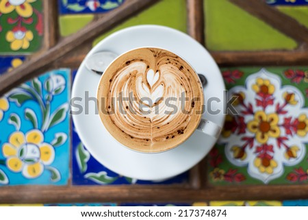 A cup of coffee in a white cup on design table - stock photo