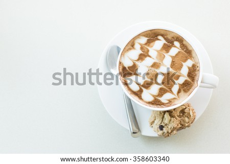 A cup of coffee in a white cup on mable table.