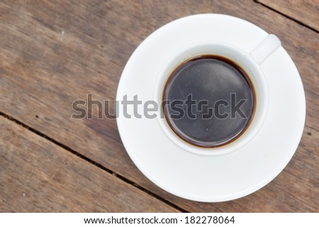 A cup of coffee in a white cup on wooden background
