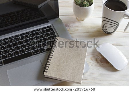A cup of coffee, laptop computer, mouse, notebook and cactus on wooden table  - stock photo