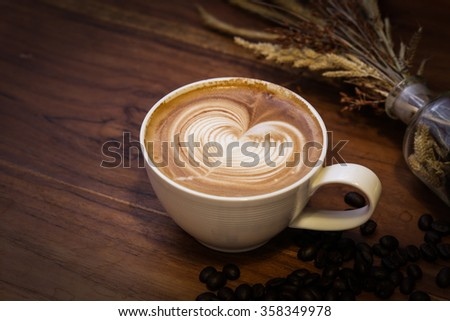 A cup of coffee latte with heart pattern in a white cup on wooden background - stock photo